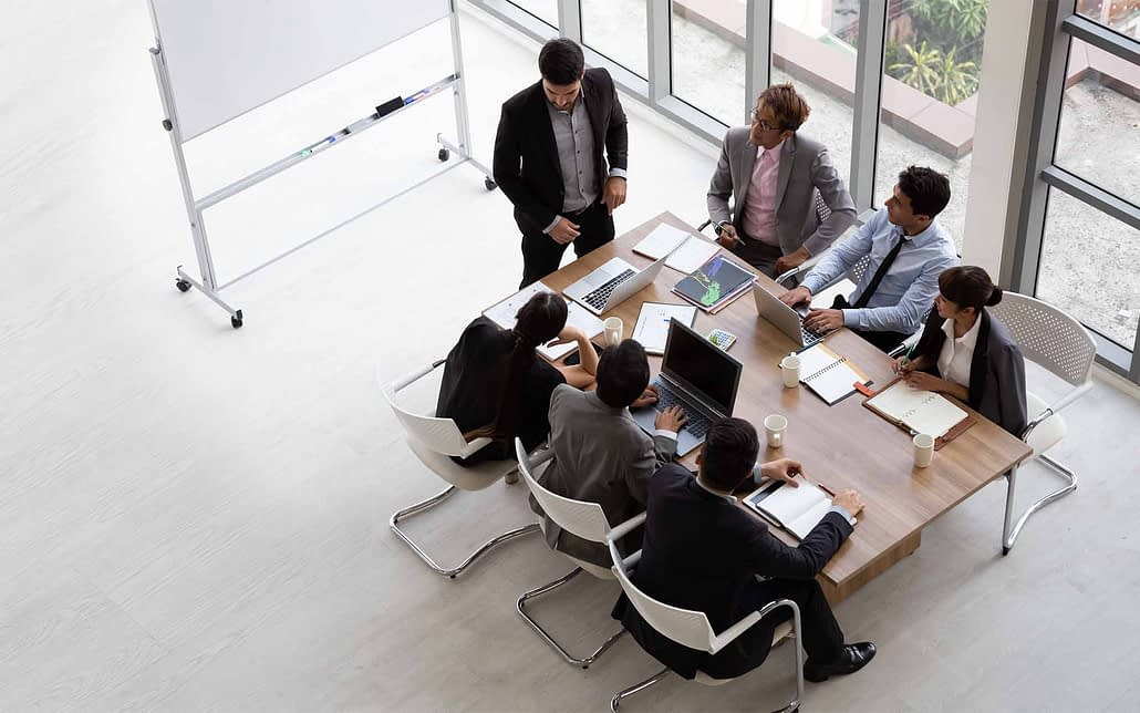 Group of workers from an angle at a smaller table having a meeting